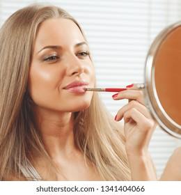 Beautiful woman applying makeup looking at mirror - close up