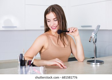 Beautiful woman applying makeup in the morning