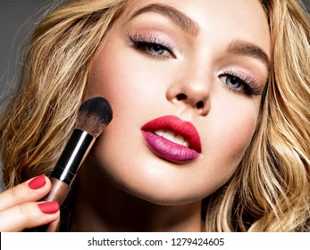 Beautiful woman applying makeup. Makeup.  Pretty girl with blue eyes.  Fashion make-up.  Closeup portrait. Gorgeous face of an attractive fashion model. Beauty concept.