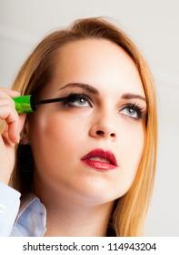 Beautiful woman applying mascara on her long eyelashes