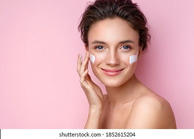 Beautiful woman applying moisturizer cream on her face. Photo of smiling woman with perfect makeup on pink background. Beauty concept