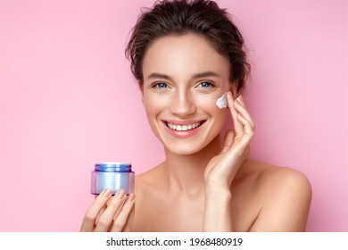 Beautiful woman applying moisturizer cream on her face. Photo of woman with perfect skin on pink background. Beauty and Skin care concept