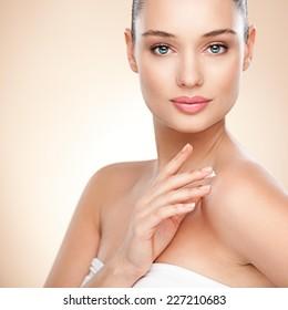 Beautiful woman applying moisturizer on her skin. Close up.
