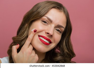 Beautiful woman applying a moisturizing cream