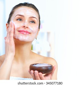 Beautiful Woman Applying Natural Homemade Facial Mask at home. Spa and Skin care concept