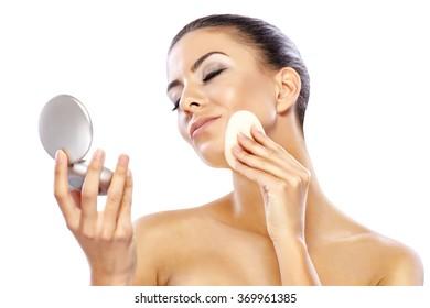 Beautiful woman applying powder