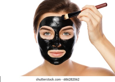 Beautiful woman is applying purifying black mask on her face over white background