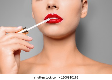 Beautiful woman applying red gloss on lips against gray background, closeup