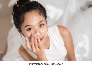beautiful woman applying some cream to her face for skin care
