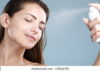 Beautiful woman applying spray  water treatment on face on blue background