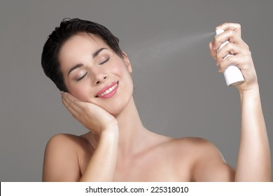 Beautiful woman applying spray water on face on neutral background