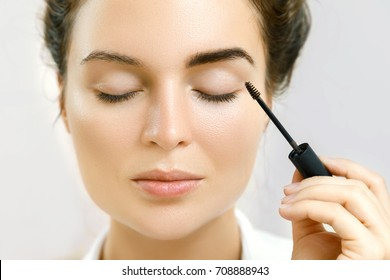 Beautiful woman is applying tinted eyebrow gel
