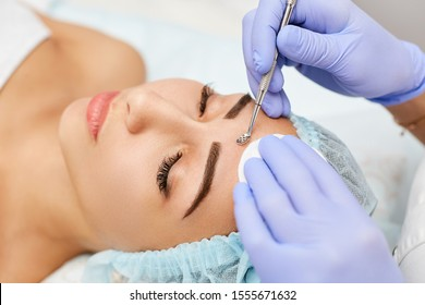 Beautiful woman at the appointment with a dermatologist. Removing blackheads in a beauty salon. Beautician at work.