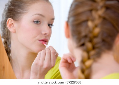 Beautiful woman appying lip gloss on her lips and looking into mirror