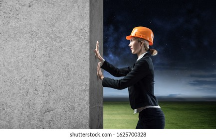 Beautiful woman architect pushing concrete wall. Young beautiful specialist in safety helmet move cement block. Sale building material and services. Grey concrete wall as banner with copy space.