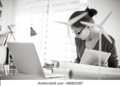 Beautiful woman architect, working on an ecological construction project in her office. There are models of wind turbines in the foreground. Black and white picture