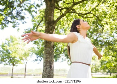 Beautiful woman with arms outstretched in park
