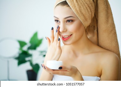 A beautiful woman asia using a skin care product, moisturizer or lotion and Skincare taking care of her dry complexion. Moisturizing cream in female hands