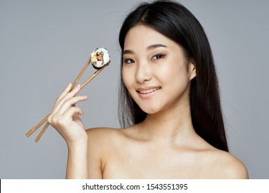 A beautiful woman of Asian appearance sushi chopsticks eating diet