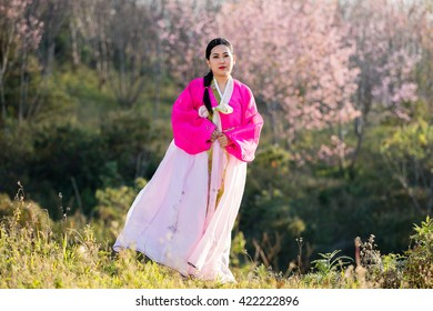 Beautiful woman asian girl Hanbok dress Korea.Woman in Korean Traditional Dress.Smiling korea woman dress traditional, outdoor shot isolated on flower background.