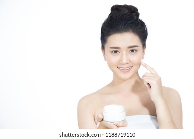 beautiful woman asian using a skin care product a white background.girl is happy with the skin cream.
