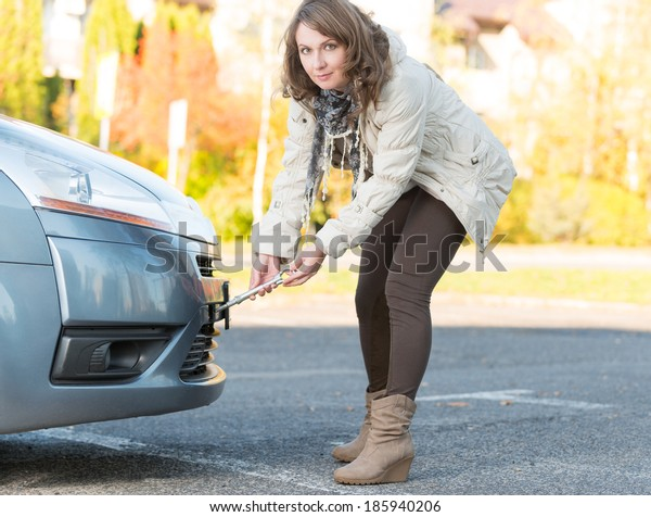 Beautiful woman assembling towing hook to a broken car