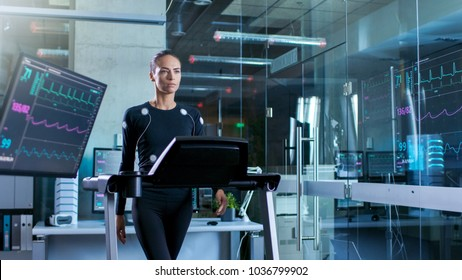 Beautiful Woman Athlete with Electrodes Connected to Her Body Walks on a Treadmill in a Sports Science Laboratory. In the Background High-Tech Laboratory with Monitors Showing EKG Readings.