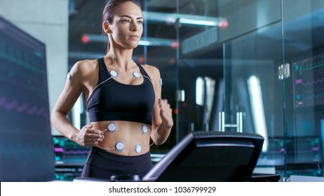 Beautiful Woman Athlete Runs on a Treadmill with Electrodes Attached to Her Body, Female Physician Uses Tablet Computer and Controls EKG Data Showing on Laboratory Monitors.