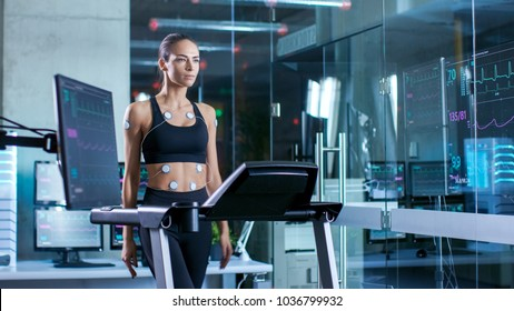 Beautiful Woman Athlete Wearing Sports Bra with Electrodes Attached to Her, Walks on a Treadmill in a Sports Science Laboratory. In the Background Laboratory with Monitors Showing EKG data.