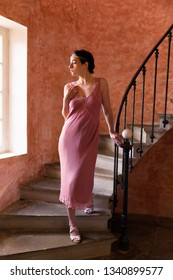 Beautiful woman in authentic retro twenties flapper dress and headband walking down an antique spiral staircase