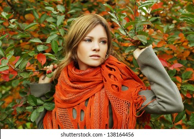 Beautiful woman in autumn foliage, fashion portrait