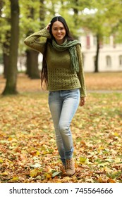 Beautiful woman in autumn landscape walking through leaves