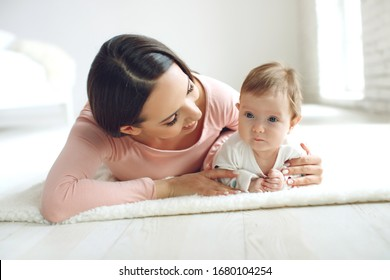 Beautiful woman with a baby is resting in a cozy house.