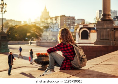 Beautiful woman in the background of a European city in the sun at sunset, student and traveler, vacation in the city, Moscow, Russia