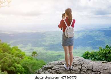 Beautiful woman with backpack standing on the cliff edge and taking a photo.