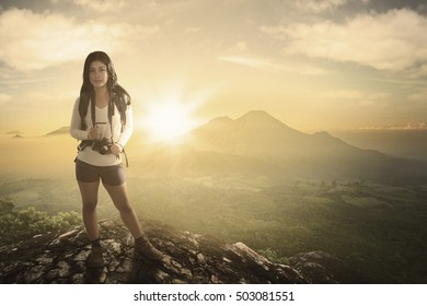 Beautiful woman backpacker carrying backpacks and camera while standing on the rock with sunrise in the background