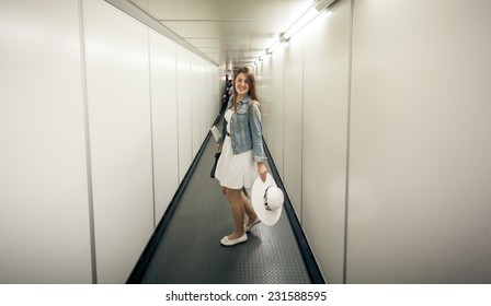 Beautiful woman with bags walking at boarding gate at airport