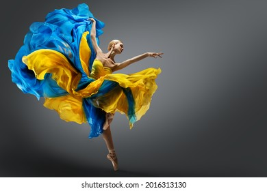 Beautiful Woman Ballet Dancer Jumping in Air in Colorful Fluttering Dress. Graceful Ballerina Dancing in Yellow Blue Gown over Gray Studio Background - Shutterstock ID 2016313130