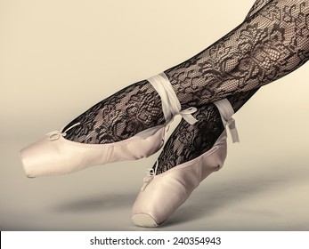 beautiful woman ballet dancer, part of body legs in shoes and black lace tights studio shot on gray background