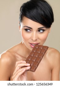 Beautiful woman with a bar of chocolate first checking to see that no one is watching her before taking the first bite isolated on beige