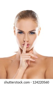 Beautiful woman with bare shoulders making a shushing gesture holding her index finger to her lips as she asks for silence or secrecy for a surprise, studio portrait isolated on white