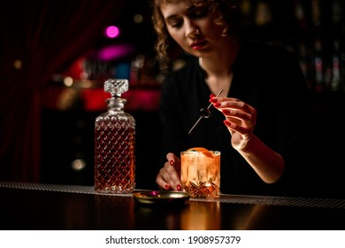 beautiful woman bartender neatly decorates glass of cold alcoholic cocktail with olive. Crystal decanter of liquor stands nearby on bar