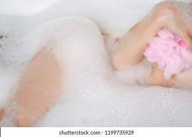 Beautiful woman in bath foam beauty health legs in gand shower sponge care body water