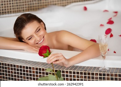 Beautiful Woman in bath with rose. Body care.
