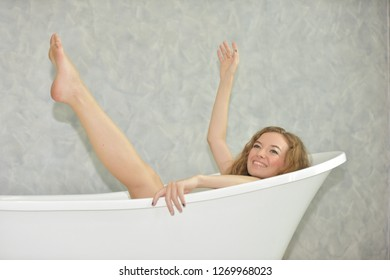Beautiful woman in the bath.Closeup view portrait of one beautiful sensual flirtatious young woman with wet hair and bright makeup lying in bath tub