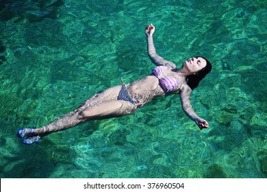 Beautiful woman bathing and  relaxing in the clear and transparent sea water. Active vacation on the beach.