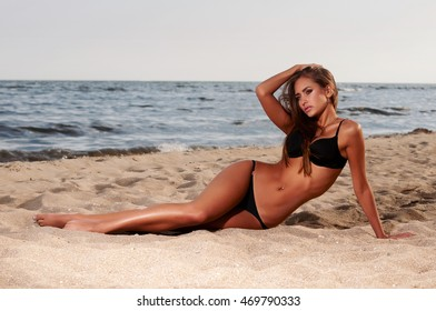 beautiful woman in a bathing suit on the beach at sunset