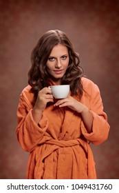 Beautiful woman in bathrobe holding cup with tea
