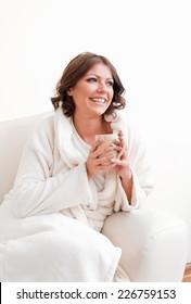 Beautiful woman in bathrobe holding a mug smiling