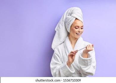 beautiful woman in bathrobe and towel on head cuts nails with nailfile, look at nails. Isolated over purple background